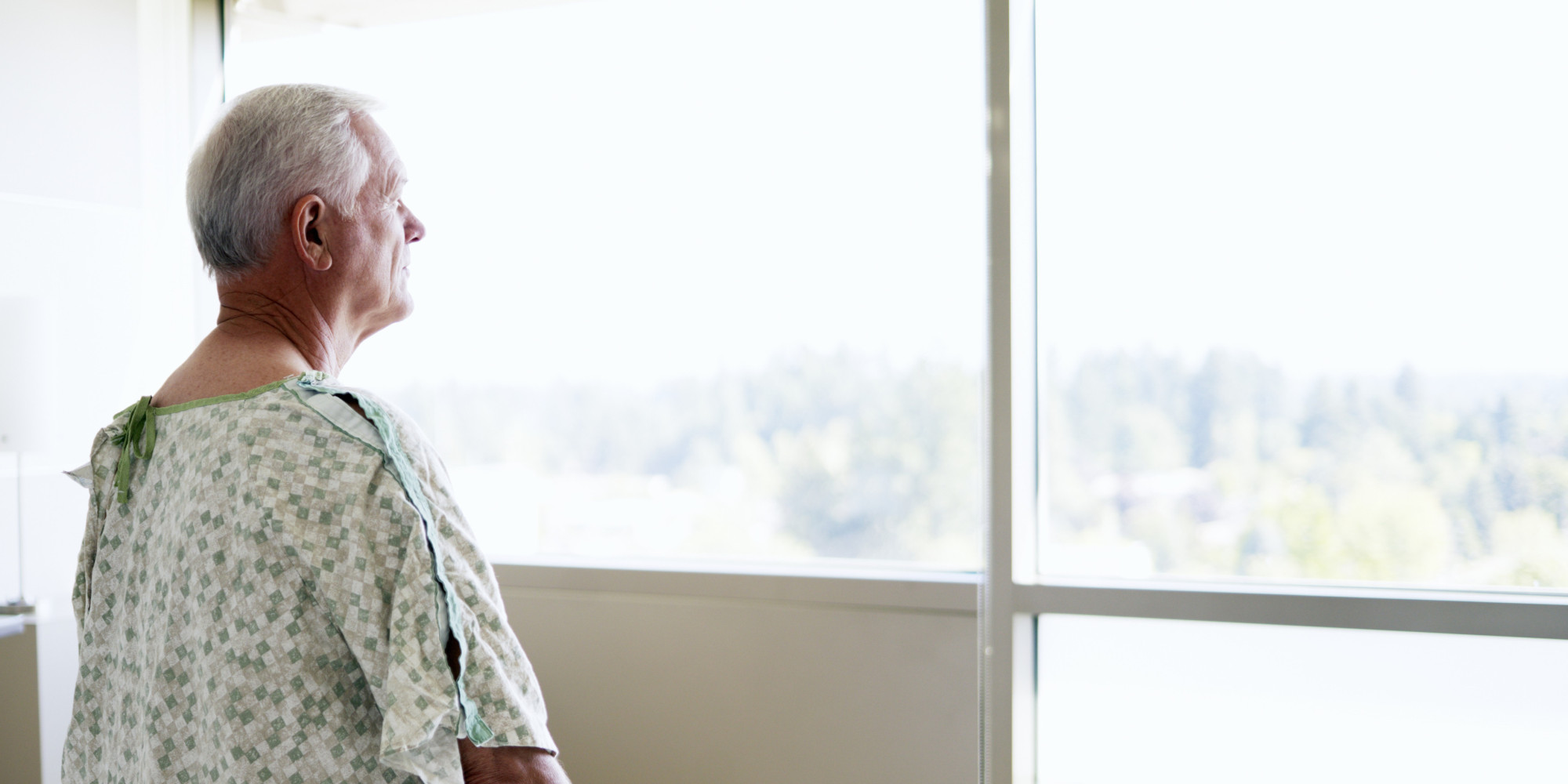 Senior male patient looking out window in hospital